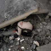 Ein Palästinenser sucht nach einem israelischen Luftangriff nach Verschütteten.