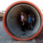 Eine israelische Mutter sucht zusammen mit ihren Kindern in einer Betonröhre in der Stadt Nitzan Schutz.