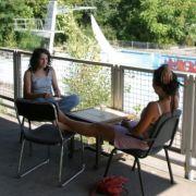Zwei Mädchen entspannen in der Bar, mit Blick auf das leere Schwimmbecken.