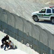 Drei Einwanderer verstecken sich am Zaun zwischen den USA und Mexiko vor der US-Grenzpolizei.