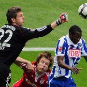 Bayerns-Torwart Jörg Butt faustet den Ball vor dem Berliner Adrian Ramos (r.).