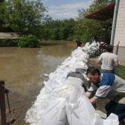 Überall ist man damit beschäftigt, mit kleinen Dämmen aus Sandsäcken die Wassermassen von den eigenen Häusern fernzuhalten.