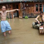 Relativ gelassen nehmen diese beiden Bewohner der Stadt Plock in Zentralpolen die Überschwemmung hin.