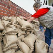 Mit Sandsäcken dichtet eine Rentnerin in Frankfurt (Oder) die Kellerfenster ihres Hauses ab.