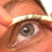 Eine Kosmetikerin wickelt die Wimpern einer Kundin auf eine selbstklebende Wimpernrolle auft. Das ist er erste Akt einer Prozedur, die etwa vierzig Minuten dauert, und in deren Verlauf zwei verschiedene Gels auf die Wimpern aufgetragen werden, die dafür s