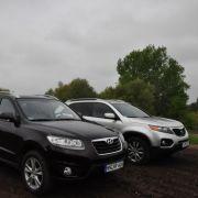 Dunkle Wolken über Hyundai Santa Fe und Kia Sorento: Kommen die beiden Straßenkreuzer auch im Gelände klar?