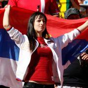 Eine Serbien-Fan steht stolz mit ihrer Flagge vor dem Spiel zwischen Deutschland und Serbien.