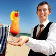 In manchen Hotels wie hier im Cliff-Hotel im Ostseebad Sellin auf Rügen muss man sich nicht einmal anstellen, wenn man einen Cocktail will. Der Barkeeper bringt ihn an den Strandkorb. Das einzige, was man selbst machen muss, ist trinken.