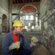 Ein Steinmetz bearbeitet mit Hammer und Meißel das Mauerwerk in der Buchardikirche.