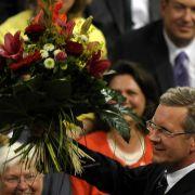 Sieg im dritten Wahlgang: Der neue Bundespräsident Christian Wulff (CDU) hält im Reichstag in der 14. Bundesversammlung einen Blumenstrauß in die Höhe.