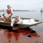 Arbeiter filtern per Hand Öl verschmutztes Wasser in Gulfport. Knapp zehn Wochen nach Beginn der Ölkatastrophe im Golf von Mexiko hatte das Öl erstmals auch die Küste des US-Staates Mississippi erreicht.