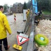 Anwohner laufen in Chemnitz über die vom Hochwasser des Flusses Chemnitz überflutete Bundesstrasse 95. Das Landeshochwasserzentrum Sachsen warnt vor rasant steigenden Flusspegeln. Besonders betroffen seien die Flussgebiete der Mulde und die