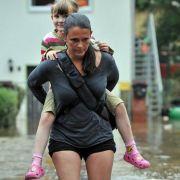 Feuchtes Huckepack: Eine Frau trägt ihr Kind auf dem Rücken über eine überflutete Straße in Chemnitz.