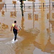 Ein Feuerwehrmann geht in Chemnitz durch den überschwemmten Schlosshof, in dem sich das Wasserschloss spiegelt.