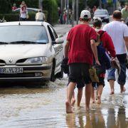 Passanten laufen am in Görlitz auf der vom Hochwasser der Neiße überfluteten Bundesstraße 99, die in Richtung Zittau führt. Auf der Altstadt-Brücke herrscht am frühen Morgen dichtes Gedränge. Die Görlitzer halten die Folgen der Flut in Bildern fest. Übera