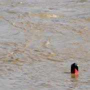 Ein Grenzpfeiler verschwindet am Sonntag auf der Uferstraße an der Neiße in Görlitz (Sachsen) im mit einem Pegelstand von rund sieben Metern historischen Hochwasser des Flusses. Auf der Altstadt-Brücke herrscht am frühen Morgen dichtes Gedränge. Die Görli