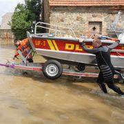 Helfer der Deutschen Lebens-Rettungs-Gesellschaft e.V. (DLRG) schieben ein Boot im Hochwasser der Neiße in Ostritz. Acht Jahre nach dem Jahrhunderthochwasser von 2002 ist Sachsen am Wochenende erneut von einer Flutkatastrophe heimgesucht worden.