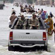...und bewaffnete Polizisten patrouillieren in den überfluteten Städten. Die Flut breitet sich unterdessen weiter aus, die Flüsse transportieren die Wassermassen vom Norden in den Süden des Landes.