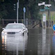 Ein Pkw steht am in Ahaus im Münsterland funktionsuntüchtig auf einer ueberschwemmten Kreuzung. Langanhaltende Regenfälle haben in Nordrhein-Westfalen zu Überflutungen gefuehrt. Wie die Bezirksregierung mitteilte, musste die Feuerwehr zu rund 2000 Einsaet