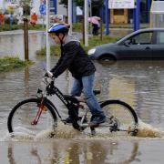 Ein Kind fährt am Freitag in Oesede bei Osnabrück ueber einen überfluteten Parkplatz auf dem noch ein Auto im Wasser steht. Starker Regen hatte den kleinen Fluss Düte über die Ufer treten lassen und die angrenzenden Gebiete unter Wasser gesetzt.