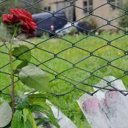 Trauer: Hinterbliebene haben fünf rote Rosen und zwei Kerzen an den Tatort gestellt.