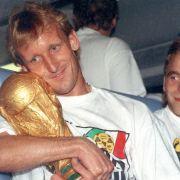 Der mit dem Pokal kuschelt: Andy Brehme, bewundernd beobachtet von Icke Häßler.