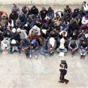 Flüchtlinge warten darauf, ein Boot nach Sizilien zu besteigen.
