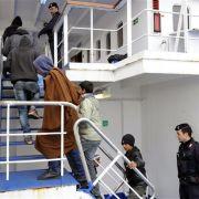 Tunesische Flüchtlinge gehen an Bord eines Schiffes, das sie nach Sizilien bringen soll.