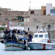 Die italienische Küstenwache nimmt vor der Küste von Lampedusa ein Flüchtlingsboot in Empfang.