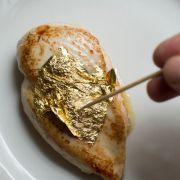 Hier wird gerade Blattgold auf ein Stück Fleisch aufgetragen.