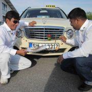 Abrar (l.) und Promod (r.) schmücken ihr deutsches Taxi wie es in ihrer Heimat in Indien üblich ist.