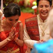 Das rote Hochzeitskleid soll dem chinesischen Brautpaar Glück bringen.