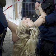 ... doch als die Femen-Aktivistinnen versuchen über den Zaun ins Kongresszentrum zu gelangen ...