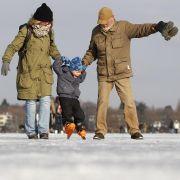 Der vierjährige Friedrich Fust (Mitte) wagt auf der zugefrorenen Außenalster mit seiner Mutter Petra (links) und seinem Grossvater Joachim erste Schritte auf Schlittschuhen.