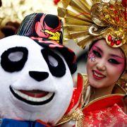 ... im Rheinland dafür die tollsten. Auch hier zeigt sich das globale Gesicht des Karnevals: Die Karnevalistin einer Delegation aus Peking macht beim Kölner Umzug mit.