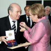 Hoch dekoriert: Kanzlerin Angela Merkel verleiht Sepp Blatter im Beisein von Theo Zwanziger (links) am 7. Juli 2006 das Bundesverdienstkreuz.