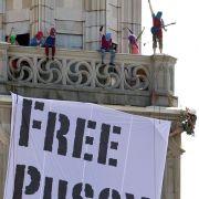 Dieses riesige Protestplakat brachte bunt vermummte auf dem Grossmünster in Zürich an.