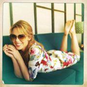 Kylie Minogue twittert sich auf einem Sofa.