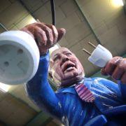 Wegen der hapernden Energiewende bekommt Umweltminister Peter Altmaier sein Fett weg: Er versucht als Pappkamerad einen Fernseher an ein Windrad anzuschließen.