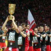 Oans, Zwoa, Drei: Den Titel-Hattrick feierten die Bayern-Spieler in Berlin mit einer Pokal-Polonäse.