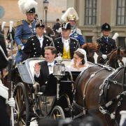 In der Kutsche, in der auch schon ihre Eltern und ihre Schwester Victoria nach deren Hochzeit durch Stockholm fuhren, begrüßt die frischvermählte Madeleine mit ihrem Mann Schaulustige am Straßenrand.