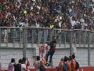 Sebastian Vettel wirft nach seinem Triumph seine Handschuhe zum Dank für die Unterstützung ins jubelnde Publikum. (Foto)
