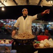 Auf den Märkten Marrakeschs, wie hier auf dem Platz Djemaa El Fna, locken zahlreiche Stände zum Kosten marokkanischer Spezialitäten ein.