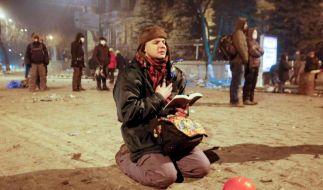 Ein Demonstrant ist mit der geöffneten Bibel in der Hand auf die Knie gegangen. (Foto)