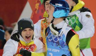 Severin Freund (M.) jubelt mit seinen Teamkollegen nach der Ergebnisbekanntgabe. (Foto)