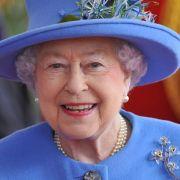 Da hat die Queen gut lachen: In ihrem himmelblauen Kostüm nebst passendem Kopfschmuck strahlt die Monarchin gut gelaunt in die Menge.