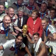 Gruppenbild mit Dame: So ausgelassen feierte Angela Merkel mit der DFB-Elf den WM-Sieg in der Kabine.