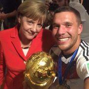 Mutti, Poldi und der Pott: Bundeskanzlerin Angela Merkel und Lukas Podolski strahlen mit dem WM-Pokal um die Wette.