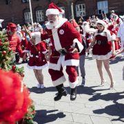 Weihnachtsmänner tanzen um den Christbaum (Foto)
