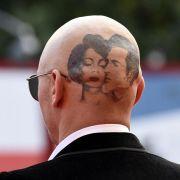 Welcher Hollywood-Schönling mag sich wohl hinter diesem Kahlkopf verstecken? Kleiner Tipp: Der Schauspieler scheint Fan von Elizabeth Taylor zu sein. Ein riesiges XXL-Tattoo prangt auf seinem Hinterkopf.